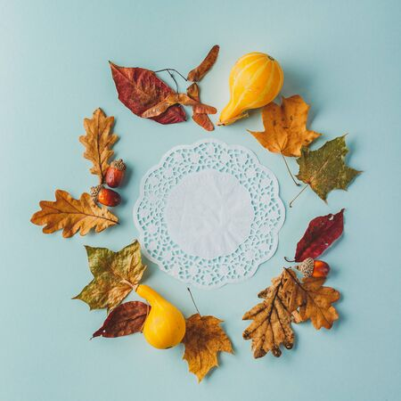 Autumn frame of maple leaves, oak, acorns and pumpkins on a blue background. Flat lay, top view, place for text