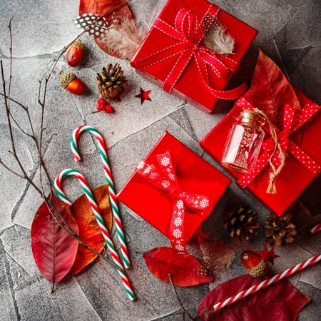 Christmas background with red gift boxes, candy canes, red autumn leaves, stars, feathers and dry twigs. Christmas background. Flat lay, copy space.