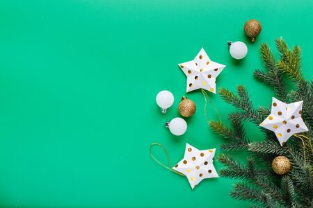 White stars in a golden dot, white and gold Christmas balls and Christmas tree branch on a green background. Flat lay, top view, copy space