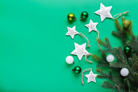 White stars in a golden dot, green Christmas balls and Christmas tree branch on a green background. Flat lay, top view, copy space 写真素材