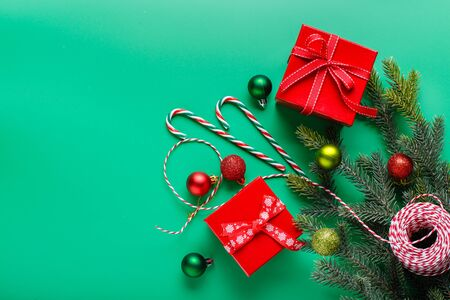 Christmas gifts in red boxes, green and red Christmas balls, candy-canes and Christmas tree branch on a green background. Christmas and New year concept. Flat lay, top view, copy space Stock Photo