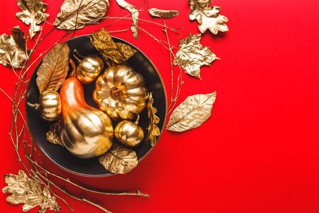 Autumn Frame with Shiny golden Decorative Pumpkins and leaves in bowl. Flat lay, top view trendy holiday concept.
