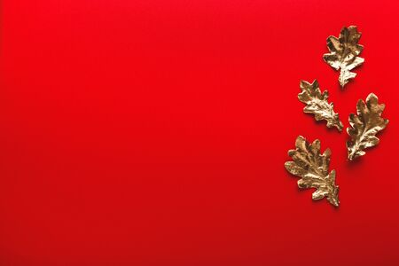 Autumn frame of golden oak leaves on a red background. Flat lay, copy space, trendy holiday concept