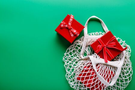 Christmas gifts in red boxes in a mesh eco-friendly bag on a green background. Christmas composition. Imagens