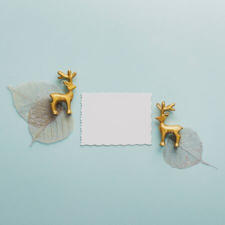 Greeting card with decorative golden deers and silver skeletonized leaves on a blue background. Christmas background. Flat lay, copy space.