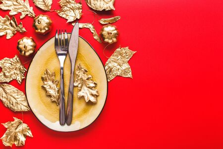 Autumn Table setting with golden leaves and pumpkins on red background