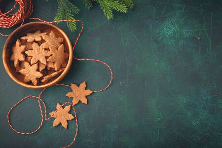 Christmas homemade gingerbread cookies in wooden bowl on dark green background with copy space for text top view. New year and Christmas postcard. Top view. Space for text. Imagens