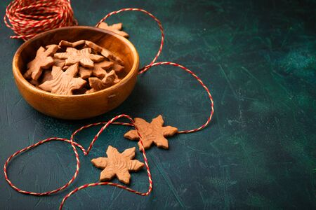 Christmas homemade gingerbread cookies in wooden bowl on dark green background with copy space for text top view. New year and Christmas postcard. Space for text. Imagens