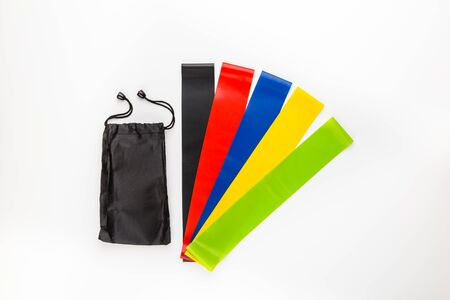 Multi-colored elastic rubber bands for fitness on a white background. A set of rubber bands of different colors - yellow, green, red, blue and black with a bag for storing them.