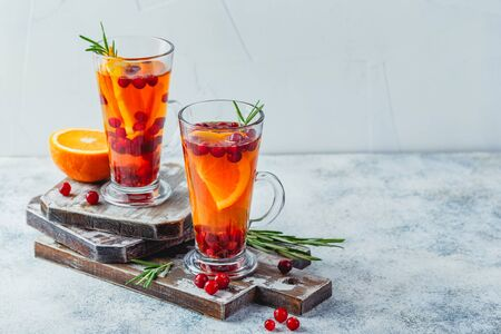 Hot tea with orange slices and cranberries in glass tall glasses. Hot drinks for winter and Christmas. Place for text