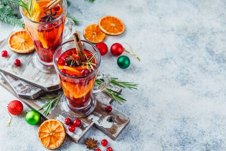 Hot tea with orange slices and cranberries in glass tall glasses. Hot drinks for winter and Christmas. Place for text.