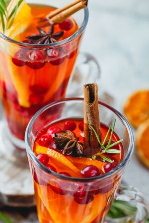 Hot tea with orange slices and cranberries in glass tall glasses. Hot drinks for winter and Christmas. Close up.