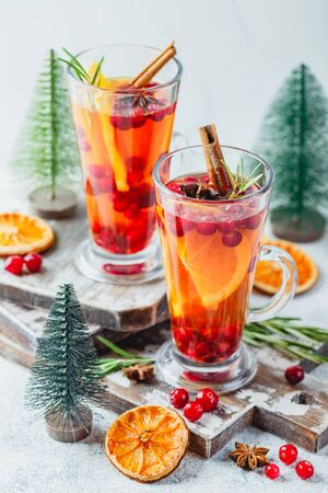 Hot tea with orange slices and cranberries in glass tall glasses. Hot drinks for winter and Christmas