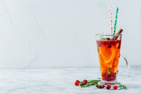 Hot tea with orange slices, cranberries and rosemary in tall glasses. Hot drinks for winter and Christmas. Place for text Imagens