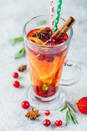 Hot tea with orange slices and cranberries in glass tall glasses. Hot drinks for winter and Christmas. Close up