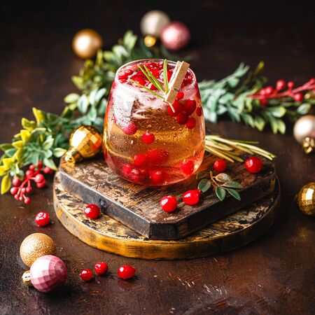 Christmas Cranberry cocktail with rosemary and ice in glass on dark backround with Christmas balls Stock Photo