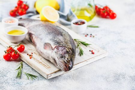 Fresh Rainbow raw trout with herbs rosemary, , tomatoes, peppercorns, olive oil, himalayan salt and lemon on light background. Healthy food. Cooking concept. Place for text.
