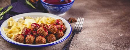 Pasta Farfalle with meatballs and cranberry sauce with spices and herbs rosemary, cinnamon and anise. Stewed meatballs in sweet berry sauce. Place for text. Long wide banner
