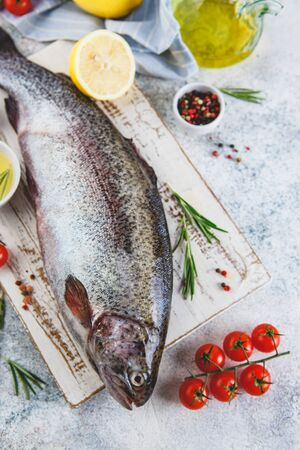 Fresh Rainbow raw trout with herbs rosemary, , tomatoes, peppercorns, olive oil, himalayan salt and lemon on light background. Healthy food. Cooking concept.