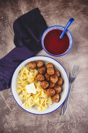 Pasta Farfalle with meatballs and cranberry sauce with spices and herbs rosemary, cinnamon and anise. Stewed meatballs in sweet berry sauce. Top view, flat lay