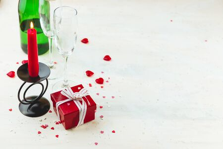 Valentines day concept, red gift box with white ribbon, wine glass, red candle and hearts jn light background, copy space.