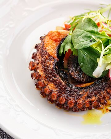 Octopus tentacle fried in a pan with new potatoes and calamata olives, garnished with green salad and spinach. Restaurant dish. Close-up