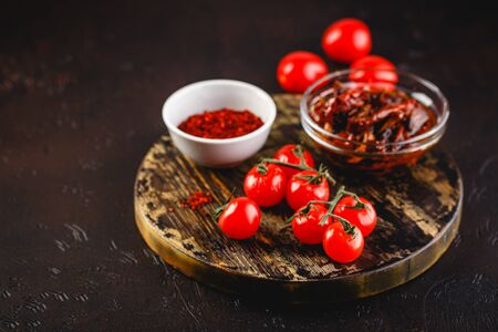 Fresh cherry tomatoes, sun-dried tomatoes and dried tomatoes with rosemary sprigs on a wooden cutting board on a dark background. Space for text. 写真素材
