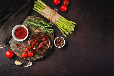 Fresh raw green asparagus and cherry tomatoes on wooden cutting board and napkin on dark brown background. Top view. Space for text. 写真素材
