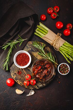 Fresh raw green asparagus and cherry tomatoes on wooden cutting board and napkin on dark brown background. Top view.