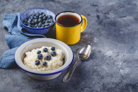 Milk rice porridge with blueberry, creamy rice pudding or french riz au lait in a metal bowl and enamel mug with tea. Place for text 스톡 콘텐츠
