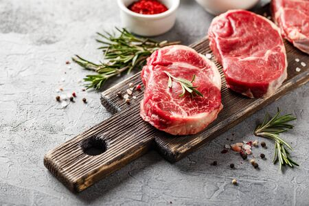 Three pieces of traditional thin steak cut from the tenderloin on wooden cutting board with olive oil, salt, rosemary and pepper. Raw Black Angus Prime meat steaks suitable for grilling or frying pan. 版權商用圖片