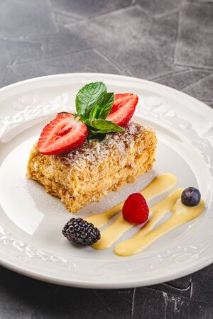 Traditional Napoleon puff cake with vanilla custard and berries, garnished with strawberries and mint in a restaurant serving. Russian cuisine, layered cake with pastry cream, close up view