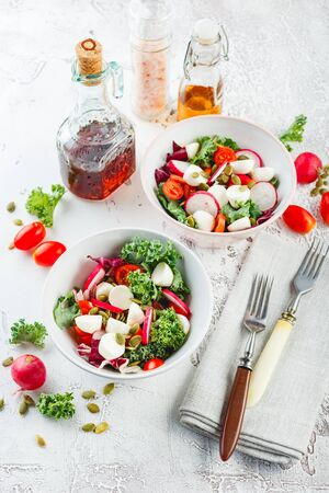 Salad from Iceberg lettuce, Kale and Radiccio, cherry tomatoes, radish, mini mozzarella and pumpkin seeds in bowls on a light background. Top view.
