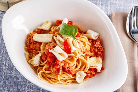 Spaghetti pasta with squid and tomato sauce and parmesan. Restaurant dish. close up Imagens