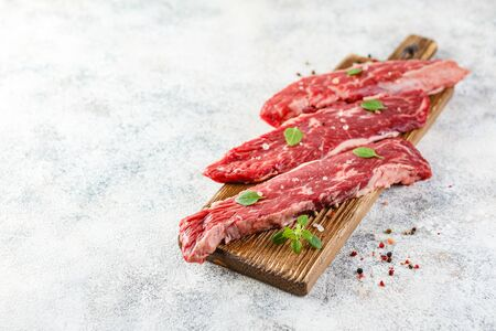 Three pieces of raw beef steak with salt on a wooden cutting board, on a light background. Premium meat, black angus steak. Space for text.