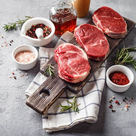 Three pieces of traditional thin steak cut from the tenderloin on wooden cutting board with olive oil, salt, rosemary and pepper. Raw Black Angus Prime meat steaks suitable for grilling or frying pan. Stock fotó
