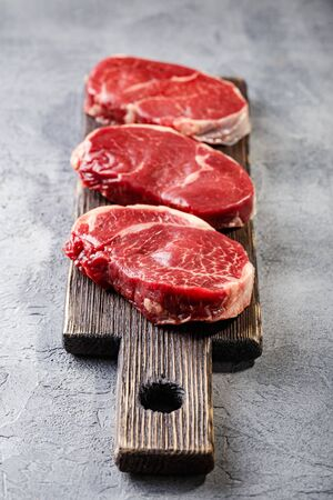 Three pieces of traditional thin steak cut from the tenderloin on wooden cutting board. The steak has good marbling, beautiful even shape and delicate meat structure for grilling or frying pan.