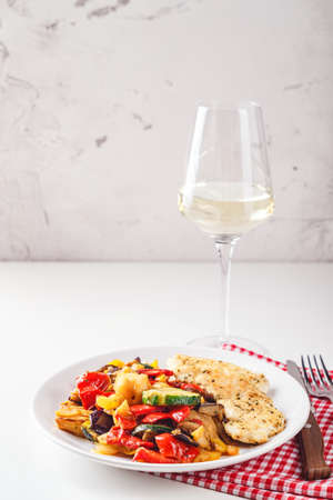 Roasted chicken breast with grilled zucchini, eggplant and red and yellow bell peppers on white plate with wine glass. Place for text. Zdjęcie Seryjne