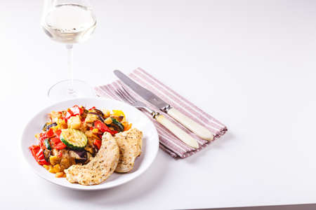 Roasted chicken breast with grilled zucchini, eggplant and red and yellow bell peppers on white plate with wine glass. Place for text. Foto de archivo