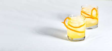 Summer refreshing cocktails, lemonade or mojito with orange zest and ice in a glass on white background. Place for text. Hard light. Long wide banner