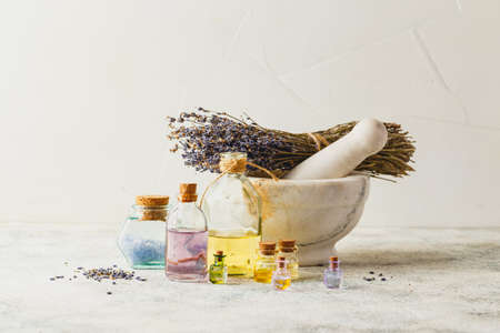 Aromatic oils in glass bottles, marble mortar and dry lavender. Concept natural ogranic skincare cosmetic. Zdjęcie Seryjne