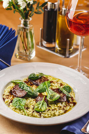 Risotto with spinach and chicken liver garnished with spinach leaves and parmesan cheese. Restaurant dish