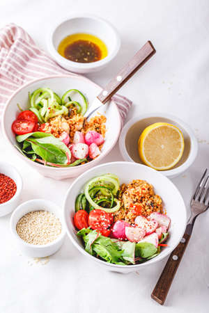Salad with couscous, chicken, tomatoes, cucumber, roasted radish and chard in bowl on white background. Healthy food. Ketogenic diet.