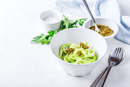 Healthy Zucchini Noddles with pesto on white background. Place for text.