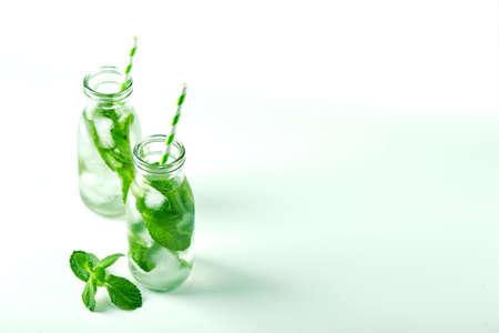 Summer drink, fresh lemonade with mint and ice in glass bottles. Mint infused water, cocktail, detox drink or lemonade Banco de Imagens