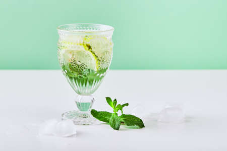 Summer drink, fresh lemonade with mint, lemon and ice in wine glass. Mint infused water, alcoholic or non-alcoholiccocktail, detox drink or lemonade. Place for text.