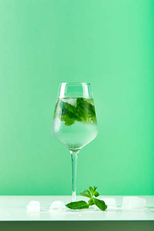 Summer drink, fresh lemonade with mint and ice in glass. Mint infused water, alcoholic or non-alcoholic cocktail, detox drink or lemonade. Place for text