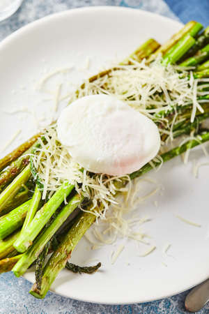 Green asparagus with poached egg and parmesan, vegetarian breakfast served on white plate on light background