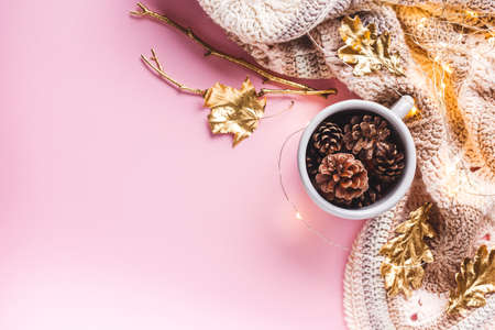 Pine cones in a gray enameled cup, gold leaves, a luminous garland and a crocheted plaid on a pink background. Flat lay, top view, Fall, Thanksgiving concept.