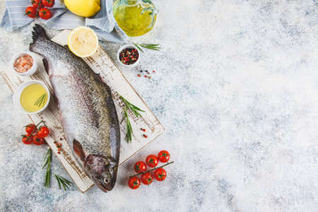 Fresh Rainbow raw trout with herbs rosemary, tomatoes, peppercorns, olive oil, himalayan salt and lemon on light background. Healthy food. Cooking concept. Top view, place for text